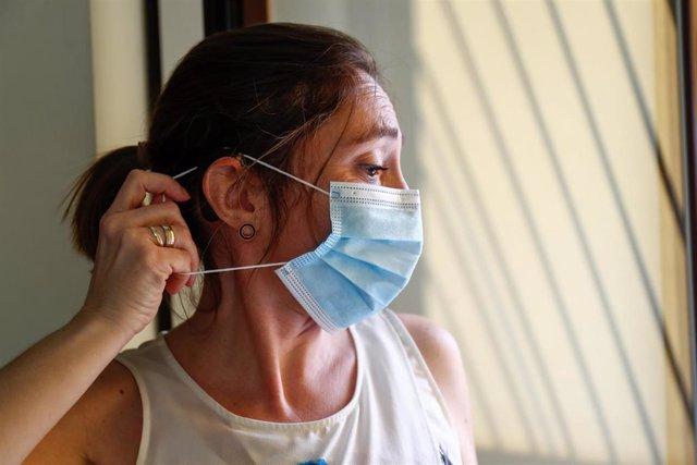 Loli, profesora, usuaria de un implante coclear y miembro de FIAPAS (Confederación Española de Familias de Personas Sordas), se coloca una mascarilla intentando que no se le enganche con el implante. En Madrid (España) a 11 de junio de 2020.