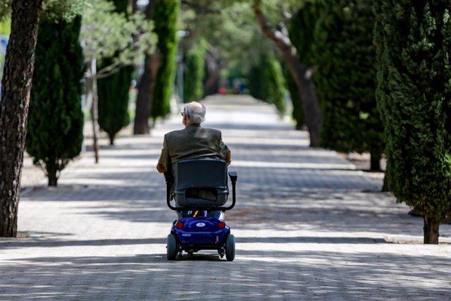 Un ancià en cadira de rodes elèctrica en un parc de Madrid (Espanya), el 2 de maig de 2020. .