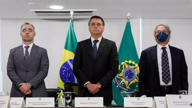 El ministro de Justicia, André de Almeida Mendonça ; el presidente de Brasil, Jair Bolsonaro; y el titular de Economía, Paulo Guedes; durante un minuto de silencio en honor de las víctimas de la COVID-19.