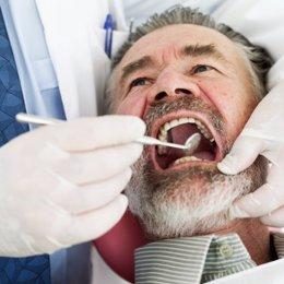 Close-up of a dentist examining a mature man