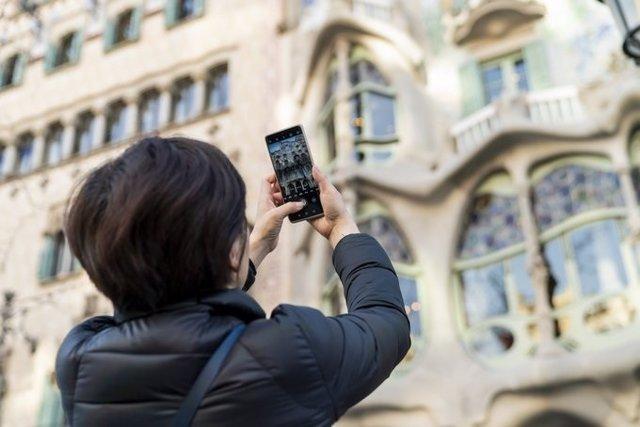 Una turista realitza una fotografia amb el seu telèfon mòbil a la Casa Batlló de Barcelona