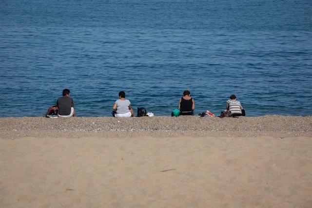 Diverses persones assegudes a la Platja de la Barceloneta respecten la distància de seguretat