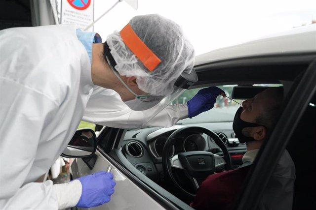 Un trabajador sanitario le realiza un test desde un vehículo a un hombre, en la zona habilitada en el Hospital de Basurto en Bilbao, donde la consejera de Salud de Euskadi, Nekane Murga, confirmó ayer que se detectaron diez positivos en COVID-19, ocho de