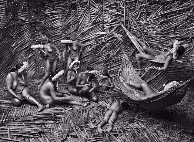 Fotografia de Sebastião Salgado: Dones del llogaret Zo?é de To-wari Ypy utilitzen la fruita vermella de la bija (Bixa orellana) per acolorir els seus cossos. Pará, el Brasil. Març i abril de 2009.