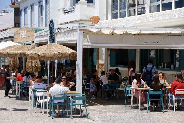 Varias personas disfrutan de la terraza de un bar en el paseo marítimo de Pedregalejo durante la Fase 1 en Málaga a 20 de mayo del 2020
