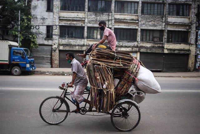 Cartoneros con mascarilla en una bicicleta en Dacca, Bangladesh