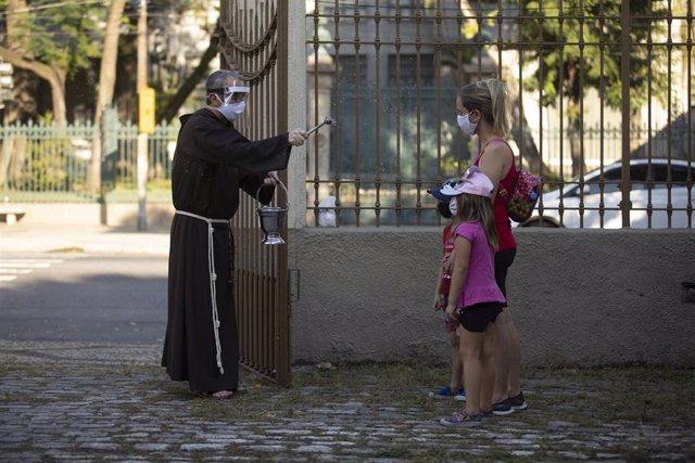Un sacerdote esparce agua bendita sobre dos feligresas en Río de Janeiro.