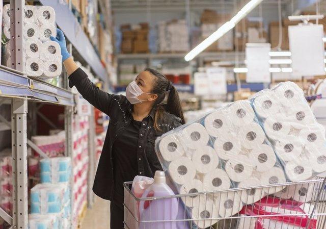 Mujer comprando papel higiénico en el supermercado.