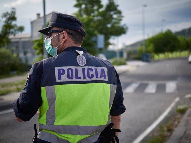 Un Policía Nacional protegido con mascarilla sanitaria durante un control de movilidad realizado en Pamplona
