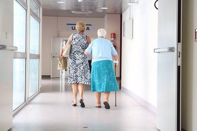 Anciana acompañada de su hija a la salida del hospital.