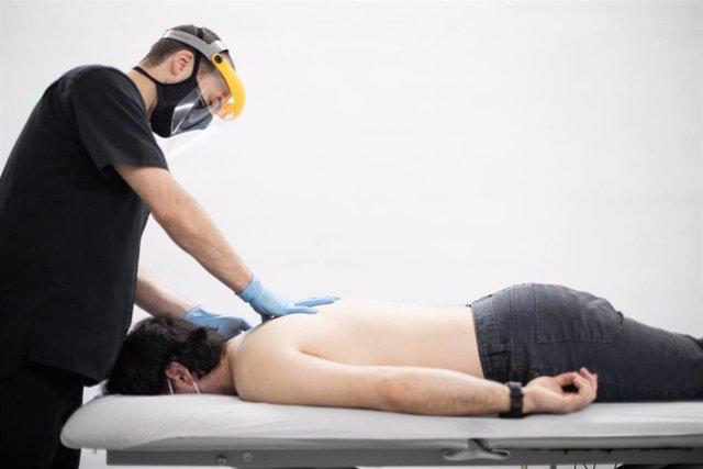 Un fisioterapeuta atiende a un cliente en su clínica, reabierta al público tras permanecer inactiva desde la declaración del estado de alarma. En Vitoria-Gasteiz, Álava, País Vasco (España), a 20 de mayo de 2020.