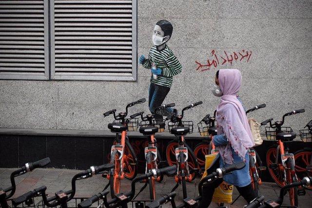Una mujer pasa ante el mural de un niño con mascarilla en Teherán