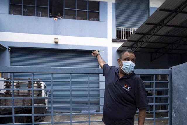 Un trabajador de una ONG ofrece ayuda a migrantes trabajadores en una residencia de Singapur.