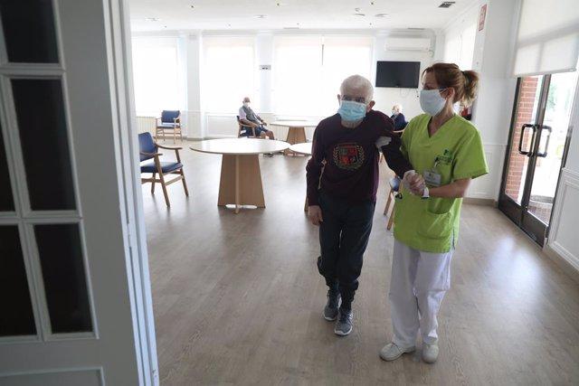 Una treballadora d'un asil ajuda a caminar a un resident durant el primer dia de visites en la Residència Centro Casaverde Navalcarnero des que es va tancar pel coronavirus. En Navalcarnero, Madrid (Espanya), a 8 de juny de 2020.