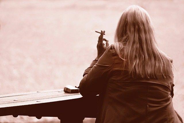 Mujer fumadora mirando al lago