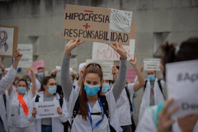 """Una sanitària sosté un cartell que demana """"Menys hipocresia i més responsabilitat"""", acompanya de desenes de membres del personal sanitari protegits amb mascarilla, durant la concentració de sanitaris en el Dia Internacional de la Infermeria (Arxiu)"""