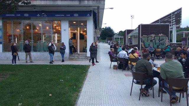Gente hace cola para sentarse en una terraza hostelera en Gijón el primer día permitido tras el Estado de Alarma