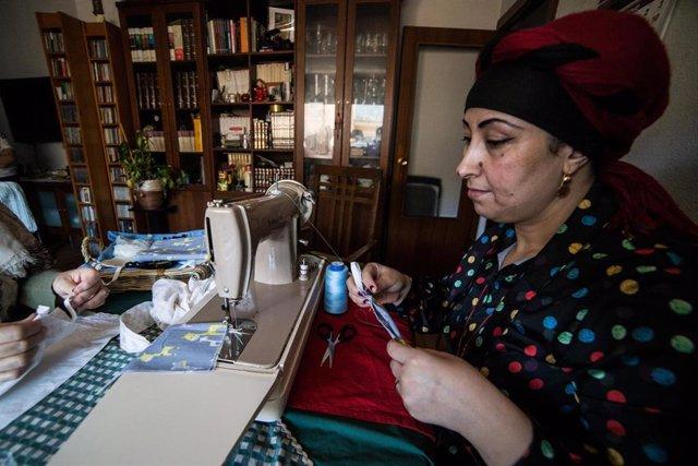 Una mujer de la ONG URDA Spain confecciona mascarillas en su casa dentro del programa 'Mascarillas refugiARTE', una iniciativa por medio de la cual mujeres refugiadas confeccionan mascarillas para protegerse del coronavirus Covid-19
