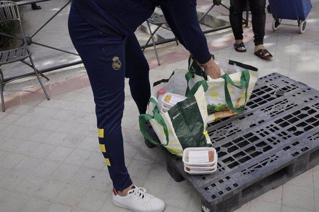 Voluntarios de la Fundación Madrina, reparten alimentos a las madres que esperan en las inmediaciones de la Parroquia Santa María Micaela y San Enrique. En Madrid, (España), a 12 de junio de 2020.
