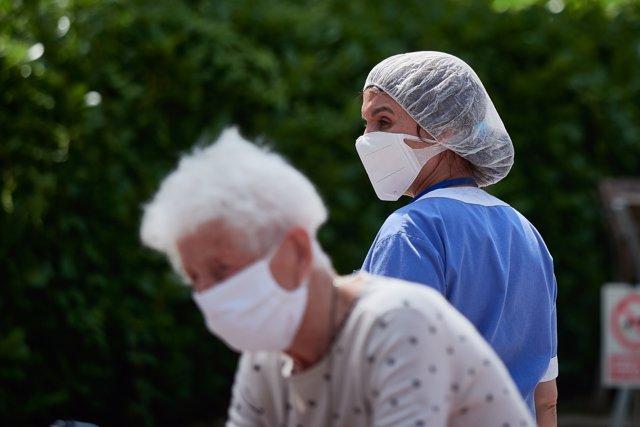 Una residente y una trabajadora sanitaria, ambas protegidas con mascarilla, de la 'Casa de Misericordia' en el exterior del centro donde han habilitado una zona de visitas
