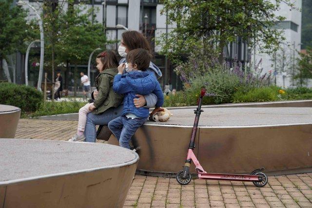 Una mujer sentada junto a una niña y un niño en un parque de Bilbao