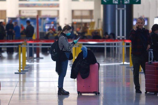 Una turista con mascarilla y guantes en el aeropuerto de Málaga este lunes 16 de marzo de 2020