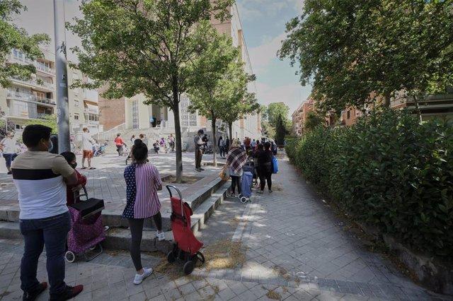 Decenas de mujeres esperan en las inmediaciones de la Parroquia Santa María Micaela y San Enrique donde la Fundación Madrina reparte diariamente unas 200 bolsas a madres y sus bebés. En Madrid, (España), a 12 de junio de 2020.