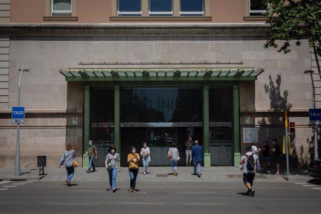 Diverses persones caminen prop de la porta de l'Hospital Clínic de Barcelona, Catalunya, (Espanya), a 27 de maig de 2020.