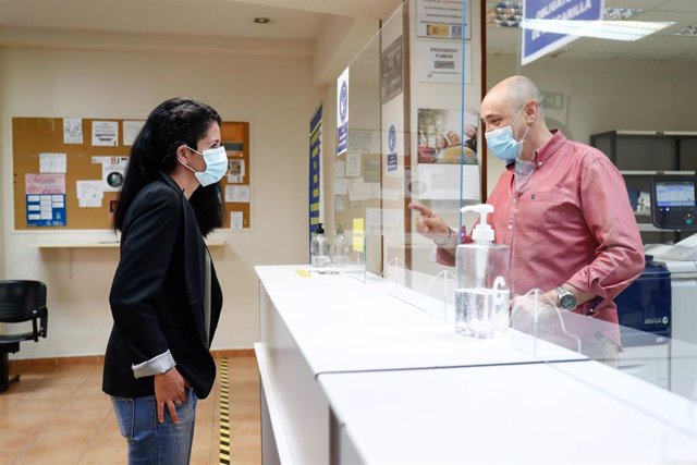 Verónica, usuaria de un implante coclear y miembro de FIAPAS (Confederación Española de Familias de Personas Sordas), habla con un dependiente de una copistería a través de una mampara. En Madrid (España) a 11 de junio de 2020.