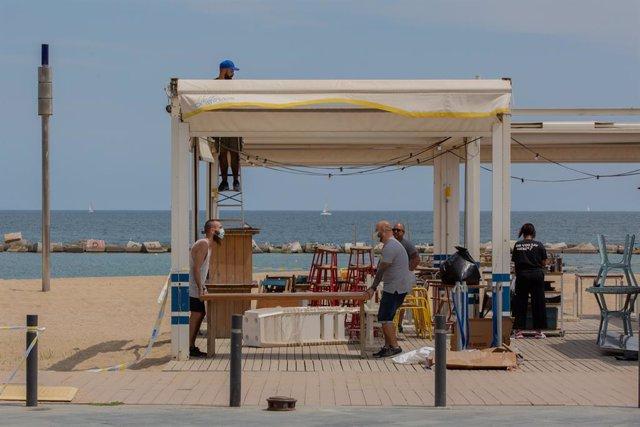 Diversos treballadors preparen la terrassa d'un bar al costat de la platja durant el segon dia de la reobertura al públic de les terrasses a l'aire lliure, a Barcelona, Catalunya (Espanya) a 26 de maig de 2020.