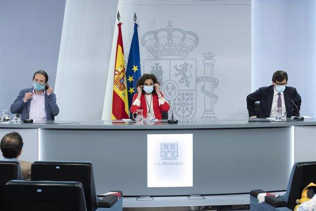 (I-D) El vicepresidente de Derechos Sociales, Pablo Iglesias; la ministra portavoz y de Hacienda, María Jesús Montero; y el ministro de Sanidad, Salvador Illa en rueda de prensa posterior al Consejo de Ministros celebrado en Moncloa.