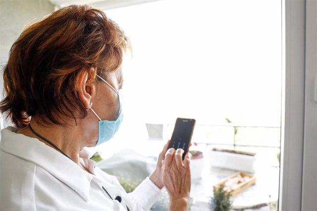 Araceli, usuaria de audífonos intracanales y miembro de FIAPAS (Confederación Española de Familias de Personas Sordas), observa su teléfono móvil desde un balcón, durante la fase 2 de la desescalada en la Comunidad, donde se está encontrando con dificulta