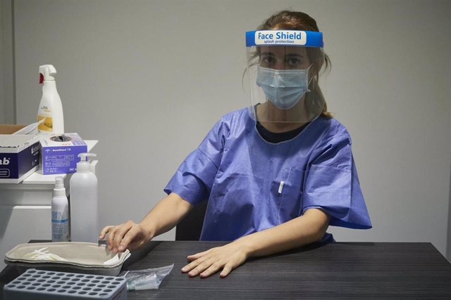 Una trabajadora sanitaria sentada en su puesto donde han acudido pacientes para realizarse una extracción de muestras en el recinto ferial REFENA de Pamplona. En Pamplona, Navarra (España), a 16 de junio de 2020.