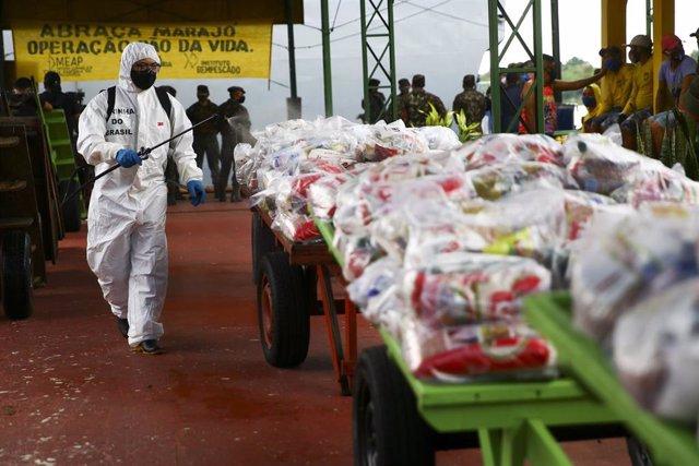 Un soldado brasileño desinfecta las bolsas de ayuda humanitaria que llegaron al municipio paraense de Afua, en el norte de Brasil, para paliar los estragos de la pandemia de la COVID-19.