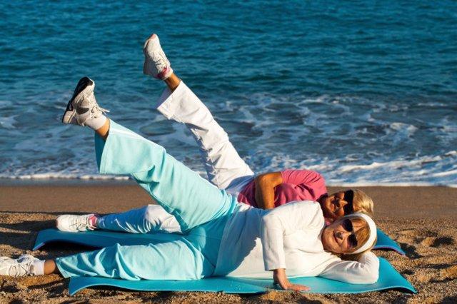 Senior women stretching legs on beach.