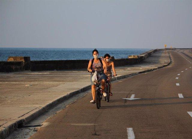 Ciclistas con mascarilla en La Habana
