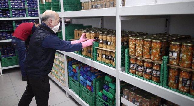 Un voluntario de la fundación FAYEC protegido con mascarilla coloca productos en el Banco de Alimentos de Madrid.