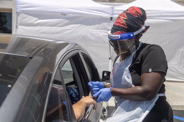 03 June 2020, US, Los Angeles: A medical worker wears protective equipment takes a sample from a person at a drive-through COVID-19 testing clinic at the Weingart YMCA Wellness and Aquatic Center. Photo: Hans Gutknecht/Orange County Register via ZUMA/dpa