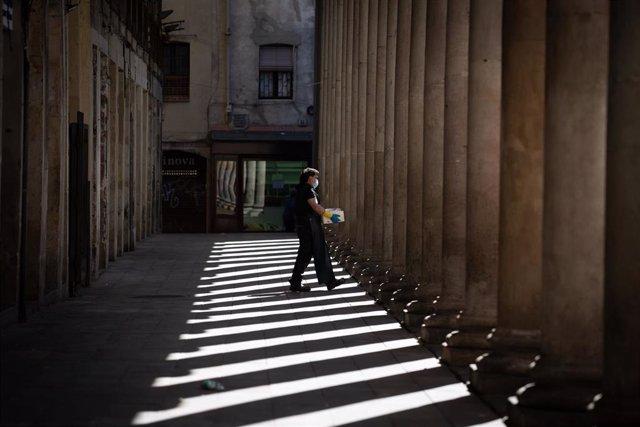 Un trabajador de un restaurante transporta una caja durante su jornada laboral en el segundo día de la reapertura al público de las terrazas al aire libre de los establecimientos de hostelería y restauración limitándose al 50% de las mesas y garantizándos