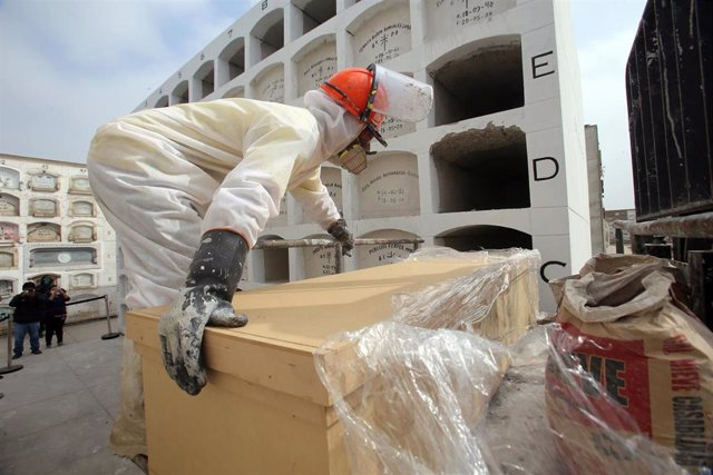 Un trabajador del cementerio de El Ángel, en Lima, coloca el cuerpo sin vida de una víctima de la COVID-19 en uno de los nichos habilitados.