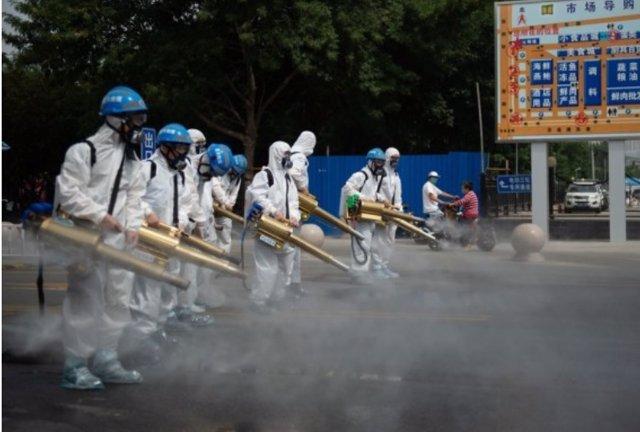 Miembros del equipo del equipo de limpieza de Pekín realizan una desinfección en el mercado mayorista de Yuegezhuang ubicado en la capital china.