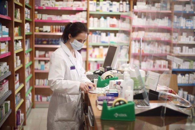 Una farmacéutica con mascarilla despacha medicamentos .