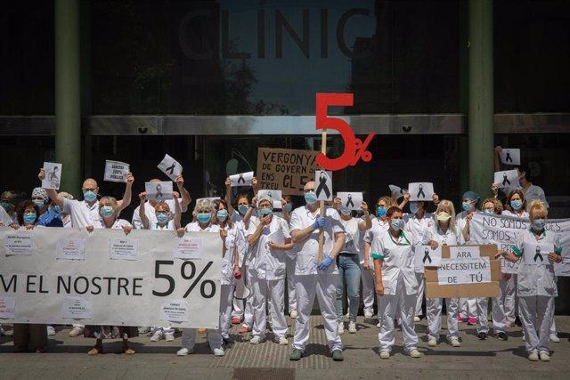 Trabajadores sanitarios protegidos con mascarilla se reúnen a las puertas del Hospital Clínic de Barcelona con pancartas y crespones negros para reivindicar contratos dignos y más personal. En Barcelona, Catalunya, (España), a 27 de mayo de 2020.