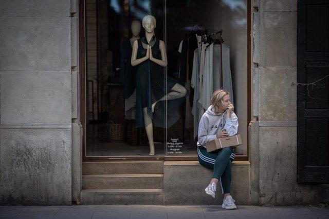 Una mujer espera a que abra una tienda de ropa, durante el segundo día de la Fase 1 en Barcelona en la que se permite reapertura de locales y establecimientos minoristas, Catalunya (España) a 26 de mayo de 2020.