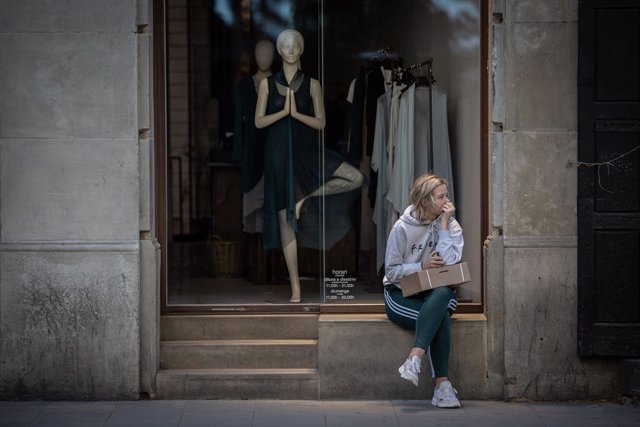 Una dona espera al fet que obri una botiga de roba, durant el segon dia de la Fase 1 a Barcelona en la qual es permet reobertura de locals i establiments minoristes, Catalunya (Espanya) a 26 de maig de 2020.