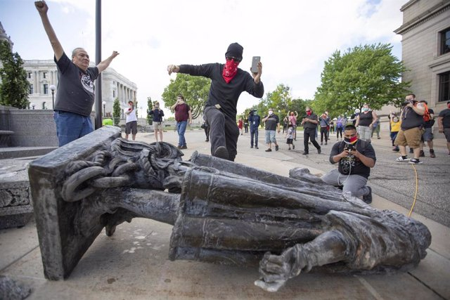 10 June 2020, US, Saint Paul: A man kicks the statue of Christopher Columbus as it lays down on the ground after being pulled down by Native American activists at the Minnesota State Capitol. Photo: Chris Juhn/ZUMA Wire/dpa