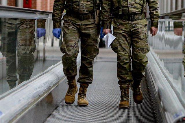 Dos militares caminan por una cinta desplazadora