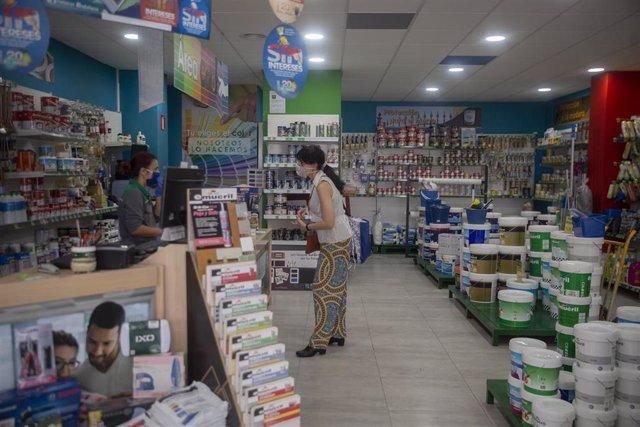 Una trabajadora de una tienda de pinturas durante el primer día desde que se decretó el estado de alarma en el que se permite la apertura con limitaciones de este tipo de comercio, entre otros establecimientos. Se atenderá a los clientes de forma individu