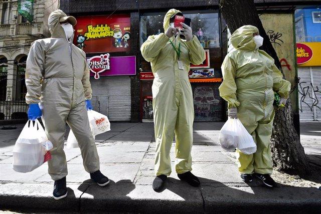 Personas con trajes protectores en La Paz, Bolivia, durante la pandemia del coronavirus.