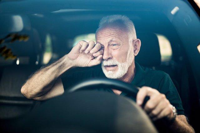 Hombre se frota los ojos mientras conduce.